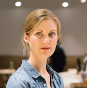 Headshot of Laura in a conference room, wearing a denim button-up shirt, smiling and looking into the camera.