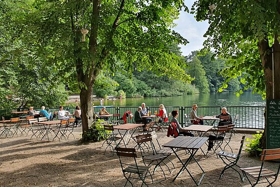 A cluster of outdoor tables and chairs, where restaurant guests are seated with beers and drinks in front of a lake, with trees all around.