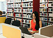 Student in a bright red-orange dress with long black hair, seated in a library in front of a black laptop. Rows of bookshelves are in the background.