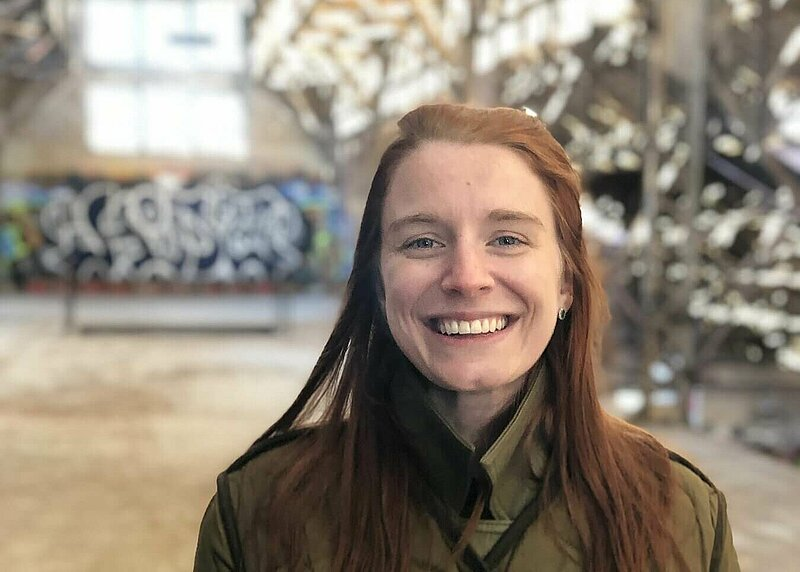 Student wearing green jacket and smiling in a hall with graffiti on wall