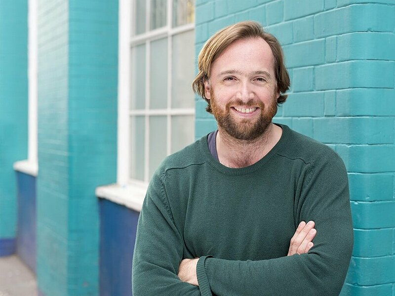 Mark smiling in a green sweater with arms crossed, in front of a turquoise brick facade and white-framed windows.