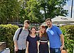 From left to right: Tom Adam, Monique Poggendorff, Jonida Popi and Gabriel Tarriba -- the Curricular Affairs team outside and surrounded by green shrubs on a sunny day.
