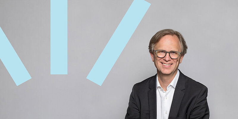 Mark Hallerberg smiling in front of a plain gray background with three blue bars on the left side.