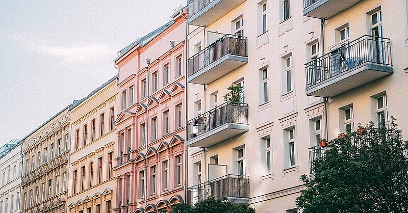 Row of white, sand, pink and yellow colored Prenzlauer Berg apartment buildings in Berlin.