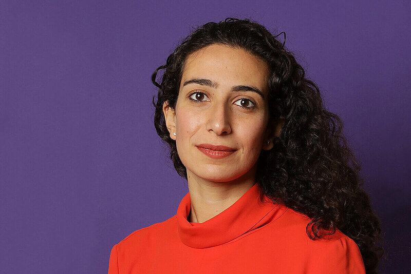 Caroline in a bright red-orange turtleneck in front of a purple background.