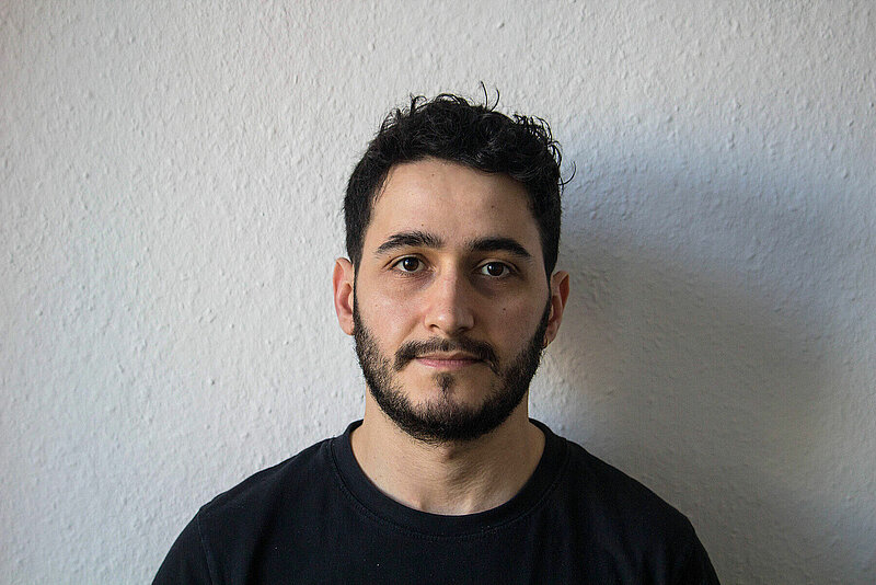 Ahmad in a black t-shirt standing in front of a white wall