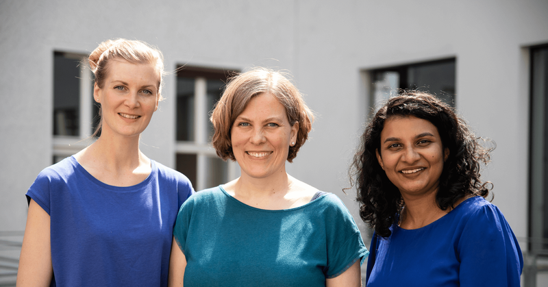 From left to right: Laura, Anne, and Fareen standing outside in front of a white wall with windows, smiling and wearing blue and teal shirts.