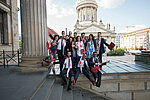 Hertie graduates smiling with open arms and diplomas in hand on steps of Berlin's Gendarmenmarkt