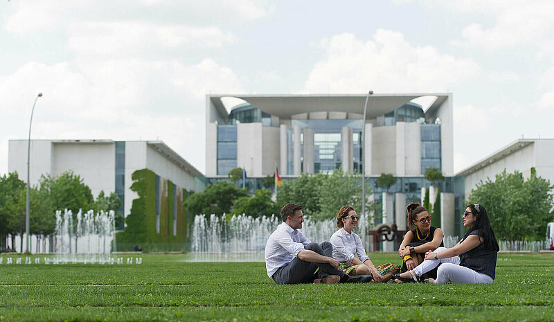 Four people sitting on green grass in front of Berlin government building Bundeskanzleramt.